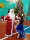Малышева Анюта наряжает Деда Мороза во время весёлой эстафеты