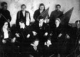 Первый любительский кружок кантелистов, созданный В.П.Гудковым из воспитанников Детского дома и школьников Петрозаводска. Слева,  с дирижерской палочкой в руках, стоит   Виктор Гудков. 1935